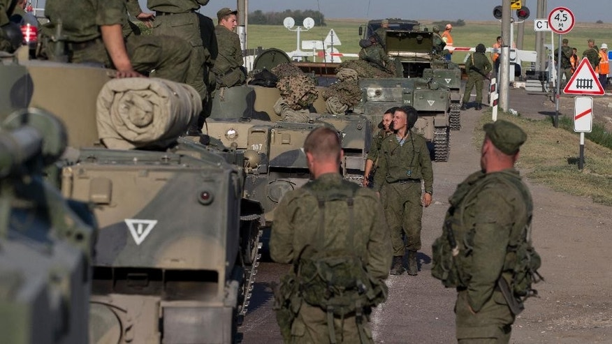 Russian solders with their several military vehicle gather at the rail road crossing about 30 kilometers (19 miles) from Ukrainian border at  Rostov-on-Don region, Russia, early Friday, Aug. 15, 2014. (AP Photo/Pavel Golovkin)
