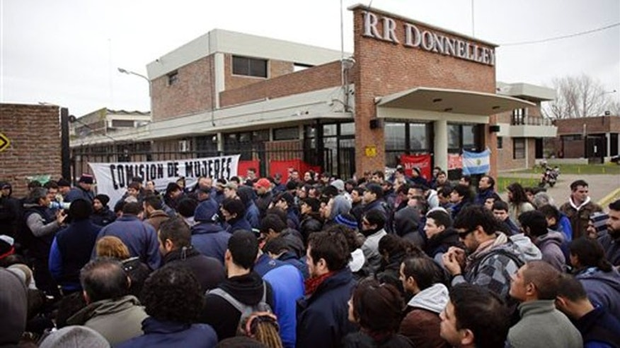 Workers outside the entrance of RR Donnelley printing plant in the outskirts of Buenos Aires, Argentina, Aug. 11, 2014.