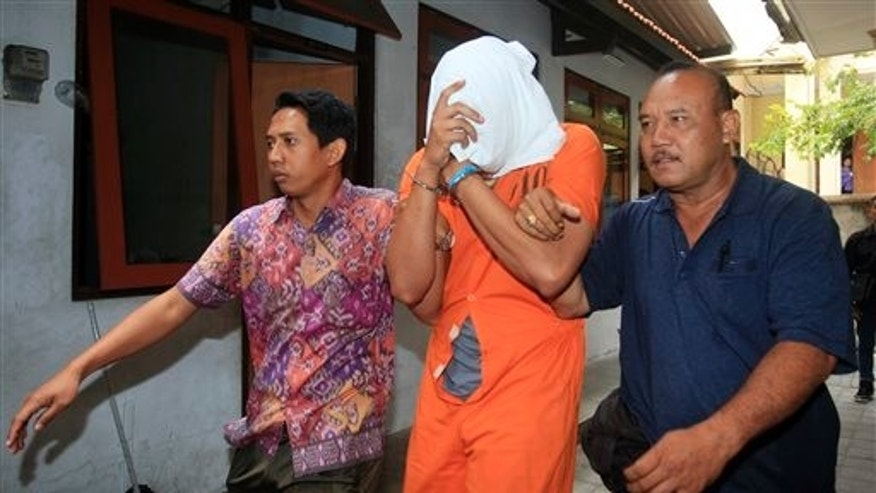 Aug. 15: Indonesian police officers escort Tommy Schaefer, center, covering his face, to a hospital for a medical check.