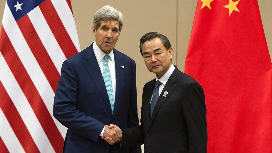 FILE - In this Aug. 9, 2014 file photo, U.S. Secretary of State John Kerry, left, shakes hands with Chinese Foreign Minister Wang Yi as they pose for photos before their meeting at the 47th ASEAN Foreign Ministers' Meeting in Naypyitaw, Myanmar. U.S. Secretary of State Kerry's address to Hawaii's East-West Center think tank this week drew attention primarily for its focus on the need for a constructive relationship with China to ensure regional peace and stability. However, Kerry touched also on U.S. relationships with four other key players in the region - Australia, Indonesia, Vietnam and the Philippines - some of them locked in contentious disputes with Beijing. (AP Photo/Nicolas Asfouri, File)