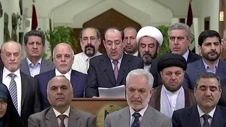 In this image taken from video, Iraq's prime minister  for the past eight years, Nouri al-Maliki, speaks at a podium surrounded by Iraqi lawmakers, Thursday, Aug. 14, 2014. Al-Maliki relinquished his post to fellow Dawa Party member Haider al-Abadi Thursday, ending a political deadlock that has plunged the country into uncertainty as it fights a Sunni militant insurgency. (AP Photo/Al Iraqiya via Associated Press Television) IRAQ OUT