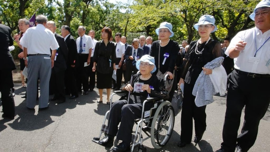 Family members of the war dead along with others arrive for a memorial ceremony for the war dead at Budokan Martial Arts Hall in Tokyo, Friday, Aug. 15, 2014. Japan marks the 69th anniversary of its World War II surrender. (AP Photo/Shizuo Kambayashi)