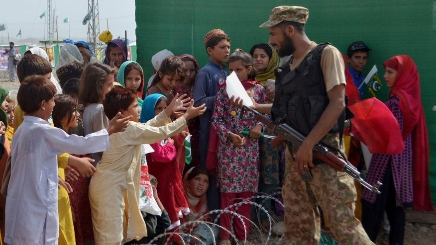 A soldier of the Pakistan army distributes a piece of ice among children displaced from Pakistani tribal area of North Waziristan, where Pakistan army is fighting against Taliban and militants, on the occasion Independence Day on Thursday, Aug. 14, 2014, in Bannu, Pakistan. Pakistanis commemorated its independence from British colonial rule in 1947. (AP Photo/Mohammad Sajjad)