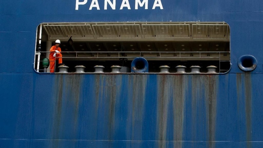In this July 24, 2014, photo, a sailor rest on the the railing as his cargo ship passes through the Miraflores Locks in Panama City. The 100th anniversary of the Panama Canal's opening Friday has been marred by increasing doubts about the country's ability to harness the full benefits of a multi-billion expansion beset by cost overruns, strikes and competition from rival projects. (AP Photo/Arnulfo Franco)