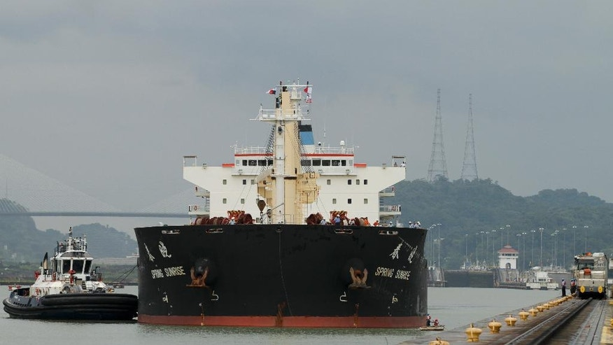 In this Aug. 4, 2014, photo, a cargo ship is approaches the Miraflores Locks of Panama Canal in Panama City. Disputes between the government and the project's European contractor, as well as labor unions, mean an already-delayed December 2015 completion deadline for the canal expansion project is unlikely to be met. (AP Photo/Arnulfo Franco)