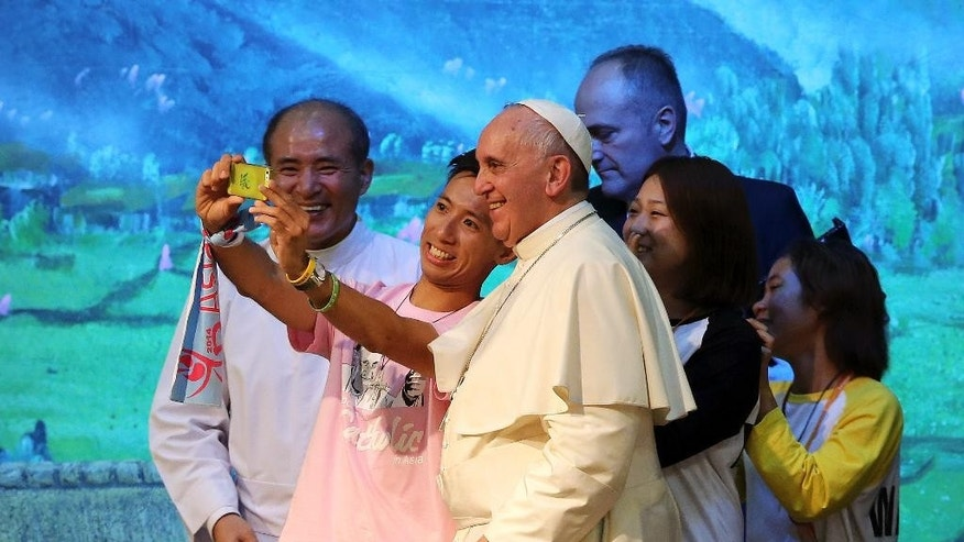 "Pope Francis poses for a selfie with young participants during a meeting with Asian youth at the Solmoe Sanctuary in Dangjin, South Korea, Friday, Aug. 15, 2014. Francis urged Catholic youth on Friday to renounce the materialism that afflicts much of Asian society today and reject ""inhuman"" economic systems that disenfranchise the poor, pressing his economic agenda in one of the region's powerhouses where financial gain is a key barometer of success. (AP Photo/Ahn Young-joon, Pool)"