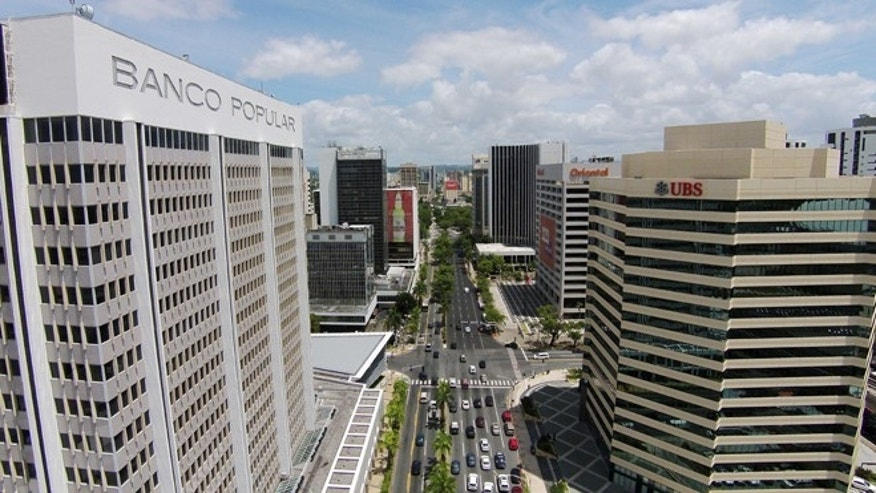 This July 16, 2014 photo shows the financial district in San Juan, Puerto Rico. Puerto Rico has seen a flurry of credit rating downgrades since the announcement of a law that allows some public corporations to restructure their debt if needed. The law was approved as the U.S. territory enters its eighth year in recession. (AP Photo/Ricardo Arduengo)