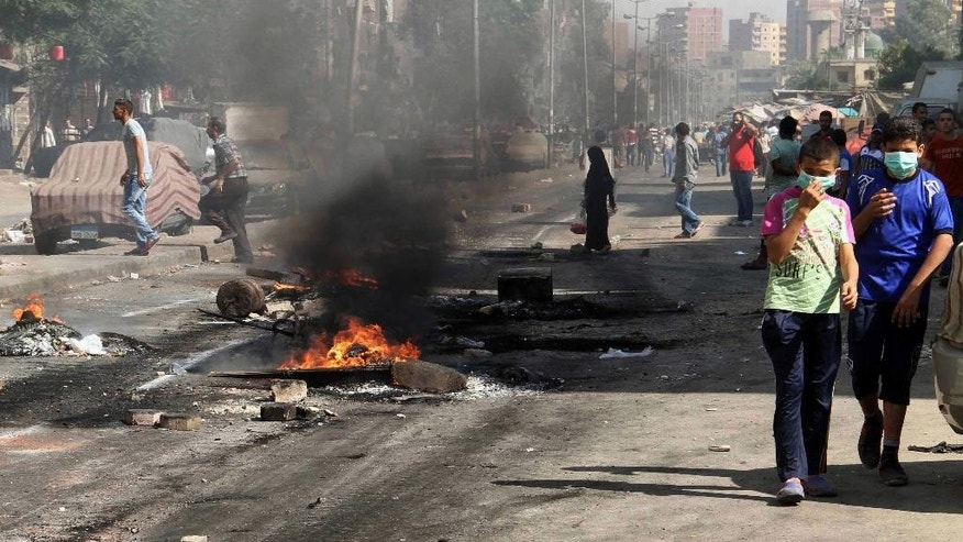 Boys walk by burning debris left on a street after clashes between Egypt's security forces and supporters of ousted President Mohammed Morsi in the Matariya neighborhood of Cairo, Egypt, Friday, Aug. 15, 2014. Islamist supporters held protests again a day after Thursday's anniversary of the dispersal of pro-Morsi sit-ins in which hundreds of demonstrators were killed. (AP Photo/Khaled Kamel)