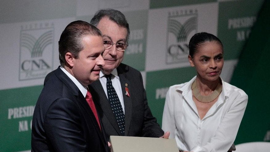 In this Aug. 6, 2014 photo, Brazilian presidential candidate Eduardo Campos, left, and his running mate Marina Silva, pose for a photo with the National Confederation of Agriculture President Joao Martins da Silva Junior, in Brasilia, Brazil. The death of Campos in a plane that smashed into a white-collar neighborhood in the port city of Santos Wednesday, Aug. 13, 2014, is reshuffling the candidates and voter preferences. Political observers say Campos' socialist party is expected to declare Silva, one of the country's most popular politicians, as its presidential candidate in the coming days. (AP Photo/Eraldo Peres)
