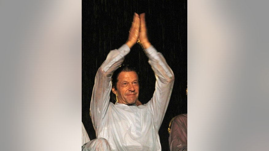 Pakistan's cricketer-turned-politician Imran Khan claps for his supporters during an anti government rally in Islamabad, Pakistan, Saturday, Aug. 16, 2014. Tens of thousands of anti-government protesters gathered in Pakistan's capital Islamabad late Friday in the pouring rain following the arrival of convoys led by Khan and a fiery anti-Taliban cleric. (AP Photo/Anjum Naveed)