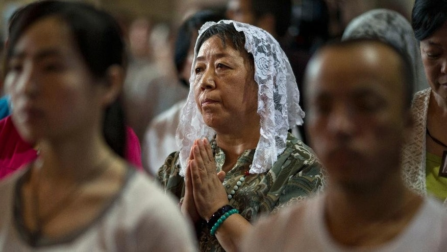 The faithful take part in a mass at the 400-year-old Cathedral of the Immaculate Conception in Beijing, China, Friday, Aug. 15, 2014. Chinese Catholics on Friday cheered Pope Francis' visit to neighboring South Korea, saying they hoped his trip to their region would help end the estrangement between Beijing and the Vatican. However, China's entirely state-run media imposed a virtual news blackout on his visit, ensuring the public at large would know little about Francis' activities. (AP Photo/Ng Han Guan)