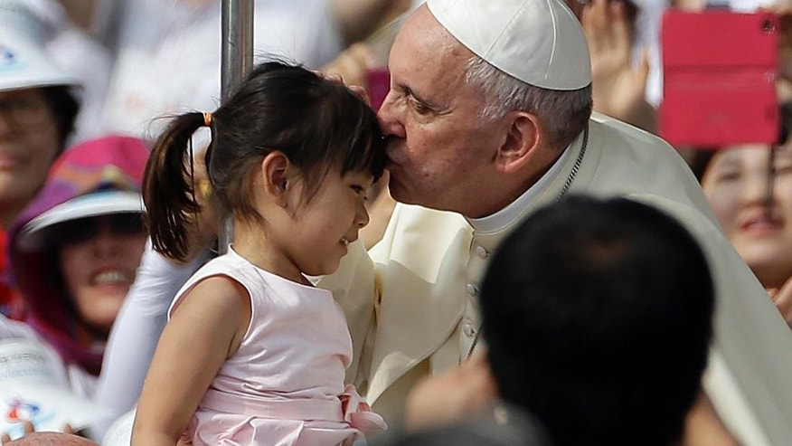 Pope Francis, right, kisses a girl as he arrives with the popemobile to celebrate a mass and the beatification Paul Yun ji-Chung and 123 martyr companions at Gwanghwamun Gate in Seoul, South Korea, Saturday, Aug. 16, 2014. Paul Yun Ji-Chung, born in 1759,  was among the earliest Catholics on the Korean Peninsula. (AP Photo/Gregorio Borgia)