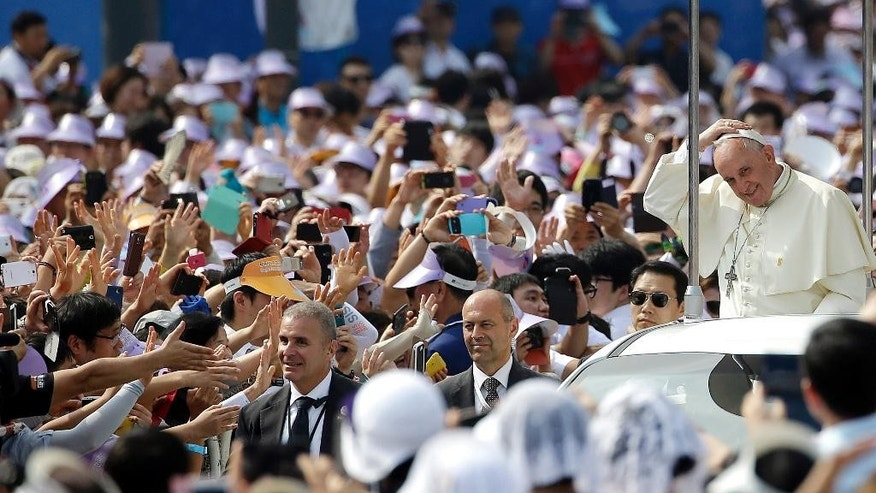 Pope Francis arrives on the popemobile to celebrate a mass and the beatification Paul Yun Ji-Chung and 123 martyr companions at Gwanghwamun Door in Seoul, South Korea, Saturday, Aug. 16, 2014. Paul Yun Ji-Chung, born in 1759,  was among the earliest Catholics on the Korean Peninsula. (AP Photo/Gregorio Borgia)