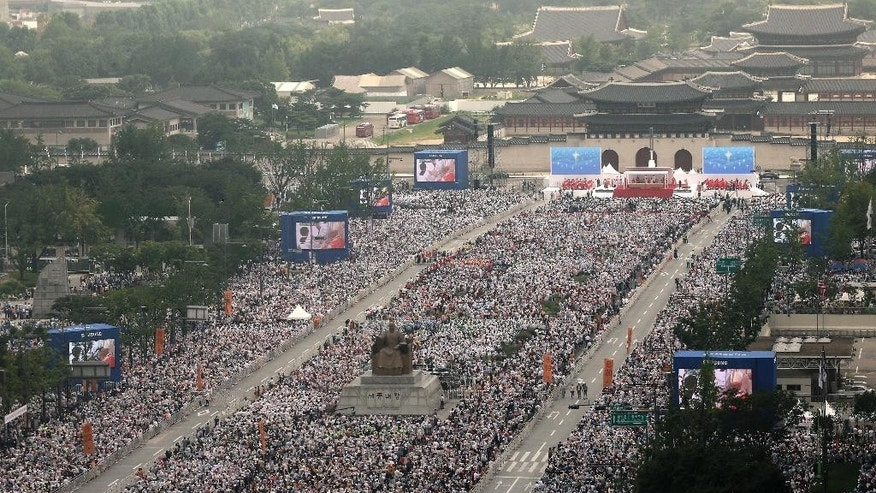 People attend a holy mass for beatification at the Gwanghwamun square in Seoul, South Korea, Saturday, Aug. 16, 2014.  Hundreds of thousands of people turned out Saturday for one of the highlights of Pope Francis' trip to South Korea: The beatification of 124 Koreans killed for their faith over two centuries ago.(AP Photo/Ahn Young-joon)