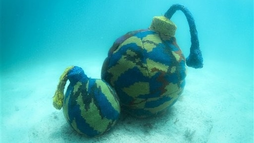In this undated photo, provided by the Polish artist Agata Oleksiak, shows her installation over an underwater sculpture at the Cancun Underwater Museum near Cancun, Mexico. The artist known as Olek, famed for slipping crocheted covers around unlikely objects has run afoul of environmental authorities in Mexico for slipping her brightly colored work around the underwater sculptures. (AP Photo)
