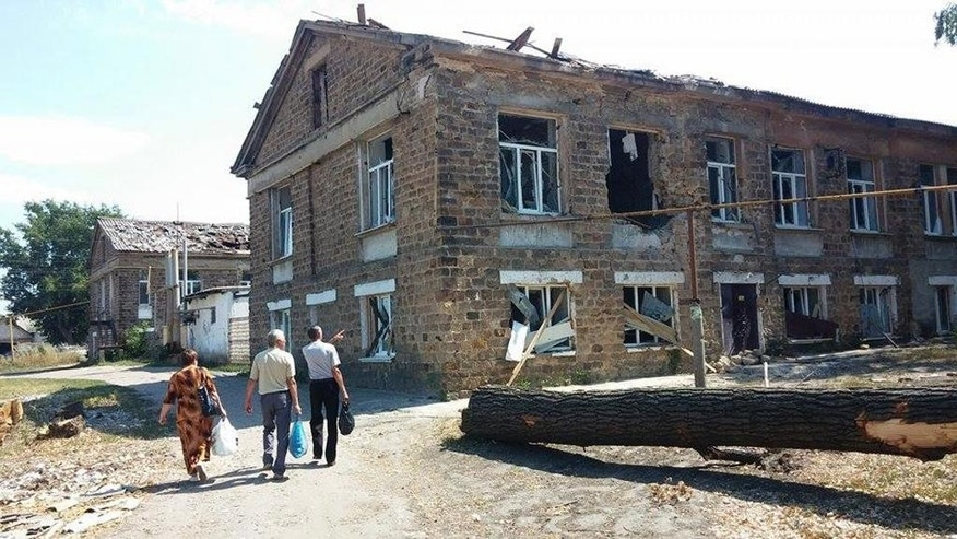 In this is image taken  Saturday Aug. 16, 2014 people walk past a local hospital in Proletarsky disrict in Lysychansk, Ukraine, that was destroyed during the fighting between the Ukrainian army and the pro-Russian rebels. Lysychansk was retaken by Ukrainian forces late last month but has seen sporadic clashes until earlier last week.  After months of rebel occupation and weeks of Ukrainian liberation, the residents of Lysychansk this shell-shocked border town say they hope simply to rebuild their former lives _ but fear the return of war to their doorstep.(AP Photo/Evgeniy Shilko)