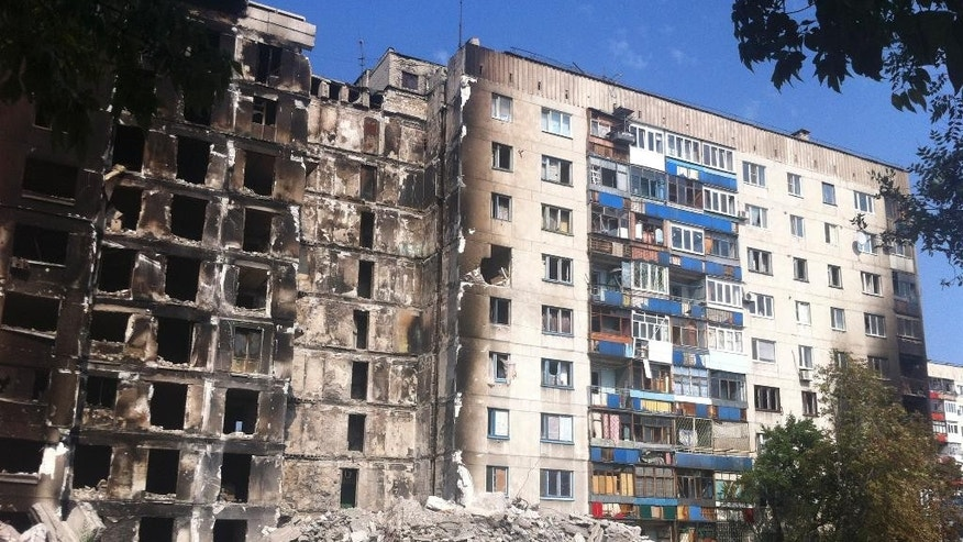 In this image taken Saturday Aug. 16, 2014 a pile of rubble stands in front of a multi storey building in a residential area in Lysychansk, Ukraine,  after it got hit by a missile during the fighting between the Ukrainian army and the pro-Russian rebels. Lysychansk was retaken by Ukrainian army late last month but has seen sporadic clashes until earlier last week. After months of rebel occupation and weeks of Ukrainian liberation, the residents of Lysychansk this shell-shocked border town say they hope simply to rebuild their former lives _ but fear the return of war to their doorstep.  (AP Photo/Vitnija Saldava)