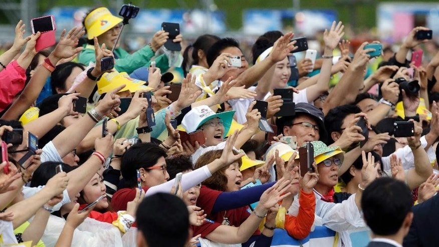 The faithful greet Pope Francis upon his arrival for the Closing Holy Mass of the 6th Asian Youth Day at Haemi Castle in Haemi, south of Seoul, South Korea, Sunday, Aug. 17, 2014. (AP Photo/Lee Jin-man, Pool)