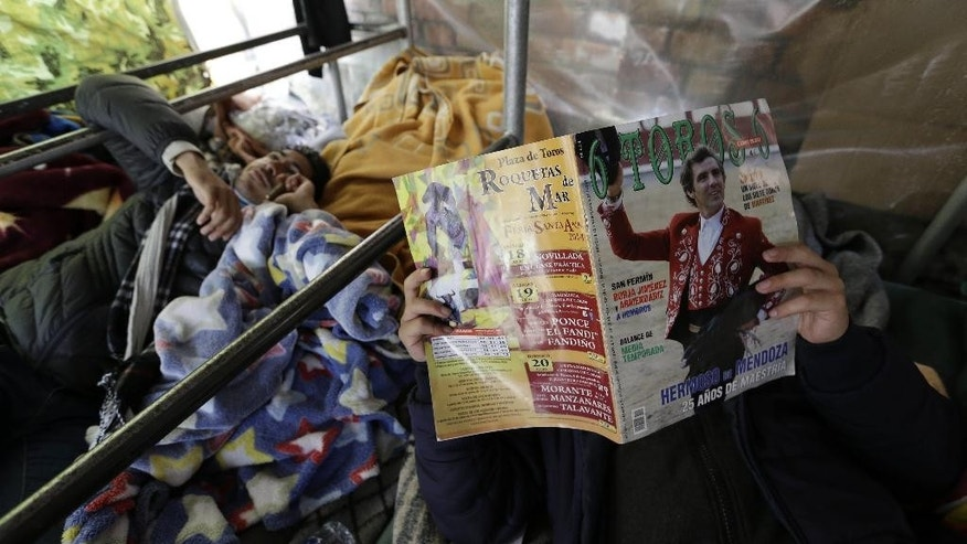 "FILE - In this Aug. 13, 2014, file photo, a Colombian bullfighter reads a bullfighting magazine as another talks on a mobile phone as they stage a hunger strike under a tent outside La Santa Maria bullring in Bogota, Colombia. Eight bullfighters have been striking for more than a week in tents outside the city's only bullring. Bogota Mayor Gustavo Petro ended bullfighting in the city when he canceled the bullring's lease in June 2012, he said he wanted public places to be used for activities of ""life, not death"". (AP Photo/Fernando Vergara, File)"