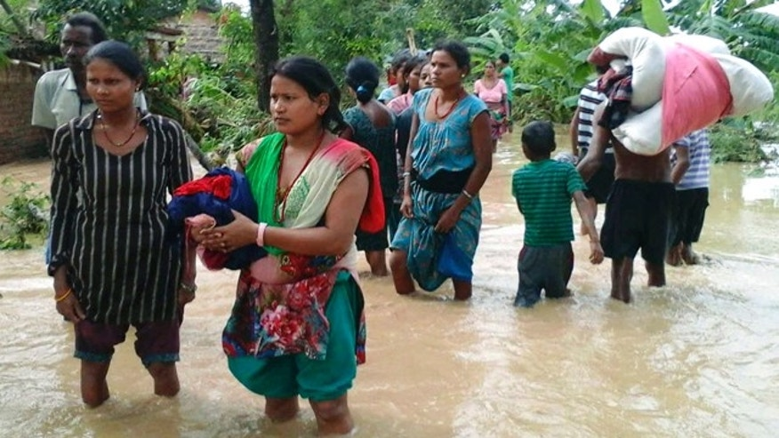 August 15, 2014: Nepalese villagers carry their belongings while wading through a flooded street to move to safer ground, at Bardia, in western Nepal.  (AP Photo/Bhabuk Yogi)