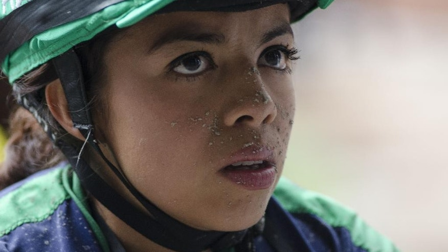 In this, July 4, 2014 photo, Jazmin Larios, 22, with dirt on her face from her ninth race as an apprentice jockey, watches a replay of her performance at the Hippodrome of the Americas in Mexico City. She placed third in the race but has yet to win one. (AP Photo/Sean Havey)