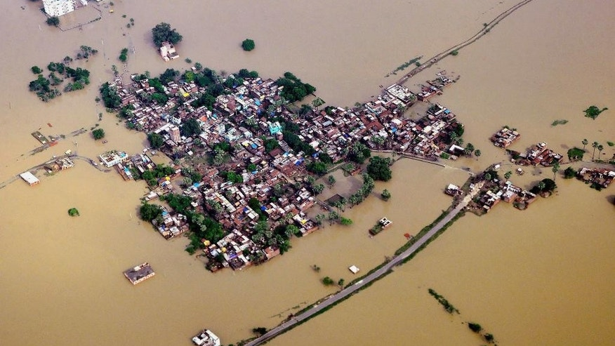 This Sunday, Aug. 17, 2014 aerial photo shows houses in a residential area partially submerged by monsoon floods at Nalanda district of Bihar, India. Rescue and relief operations continue in the state of Bihar after heavy rains caused landslides and floods in many parts of India. (AP Photo/Press Trust of India) INDIA OUT