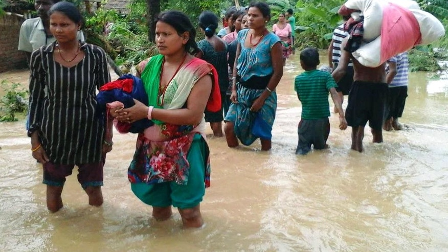 In this Friday, Aug. 15, 2014 photo, Nepalese villagers carry their belongings while wading through a flooded street to move to safer ground, at Bardia, in western Nepal. Nepalese authorities on Monday feared an outbreak of diseases as they attempted to reach thousands of people stranded by flooding that has already killed over a hundred people and left more than 136 missing. (AP Photo/Bhabuk Yogi)