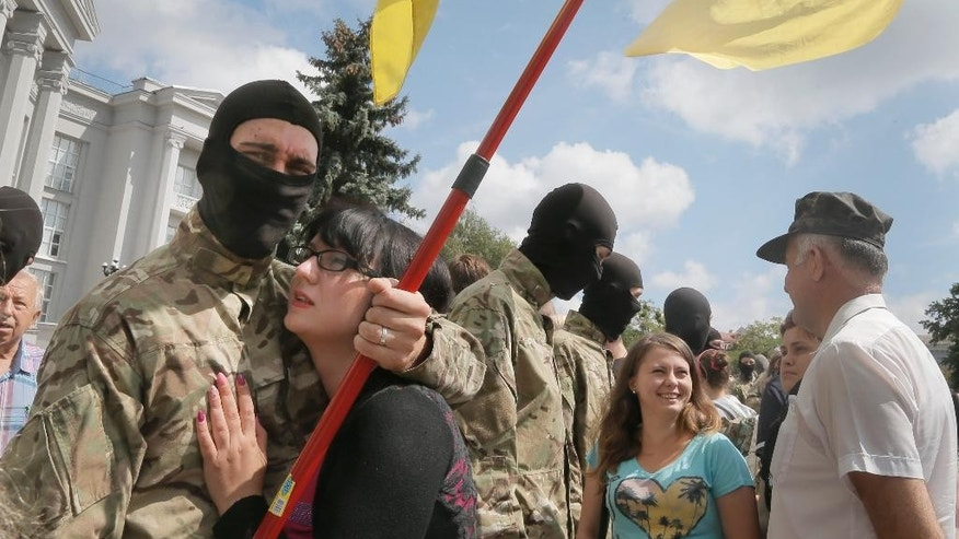 "Friends and relatives say goodbye to volunteers before they were sent to the eastern part of Ukraine to join the ranks of special battalion ""Azov"" fighting against pro-Russian separatists, in Kiev, Ukraine, Sunday, Aug. 17, 2014. Ukraine's national security council said government forces captured a district police station in Luhansk after bitter clashes, but the government also reported Sunday that separatists have shot down a Ukrainian fighter plane in Luhansk region after army troops entered deep inside a rebel-controlled city in the east. (AP Photo/Efrem Lukatsky)"