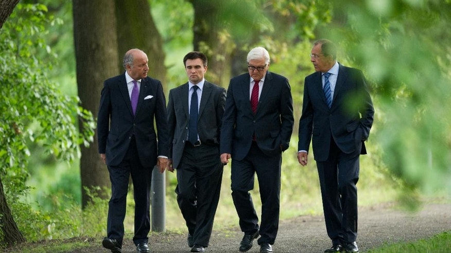 Foreign Ministers of France Laurent Fabius, Ukraine Pavlo Klimkin, Germany Frank-Walter Steinmeier and Russia Sergey Lavrov, from left, go for a walk before a meeting at the Guesthouse of Foreign Ministry Villa Borsig in Berlin, Sunday, Aug. 17, 2014. (AP Photo/Steffi Loos)