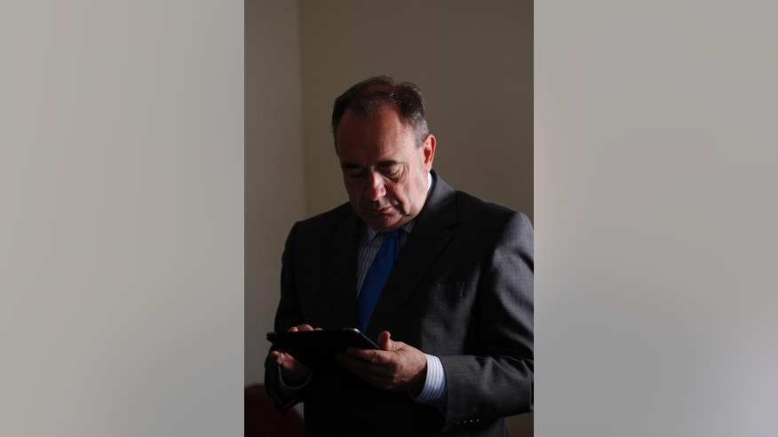 Scottish First Minister Alex Salmond checks his email on a tablet during a visit to a house building project in Arbroath on the East coast of Scotland Monday, Aug. 18, 2014. Two opinion polls show that Scotland's voters are narrowly divided on whether to leave the United Kingdom one month before a referendum. Sunday's published polls both found that a majority of decided voters want Scotland to stay within the UK alongside England, Wales and Northern Ireland. (AP Photo/Martin Cleaver)