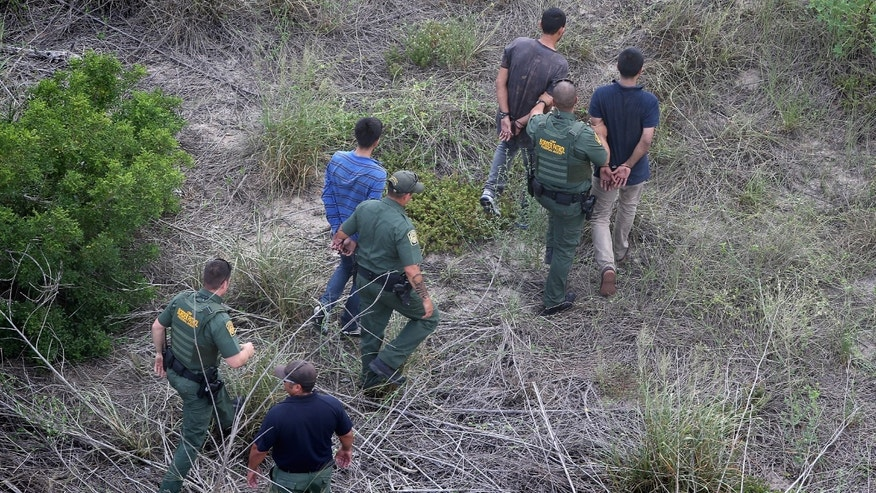 FALFURRIAS, TX - JULY 25:  U.S. Border Patrol agents detain undocumented immigrants after a foot chase on July 25, 2014 near Falfurrias, Texas. Tens of thousands of illegal immigrants have crossed into the U.S. this year, causing a humanitarian crisis on the U.S.-Mexico border. Texas' Rio Grande Valley has become the epicenter of the latest immigrant crisis, as more Central Americans have crossed illegally from Mexico into that sector than any other stretch of America's 1,933 mile border with Mexico.  (Photo by John Moore/Getty Images)