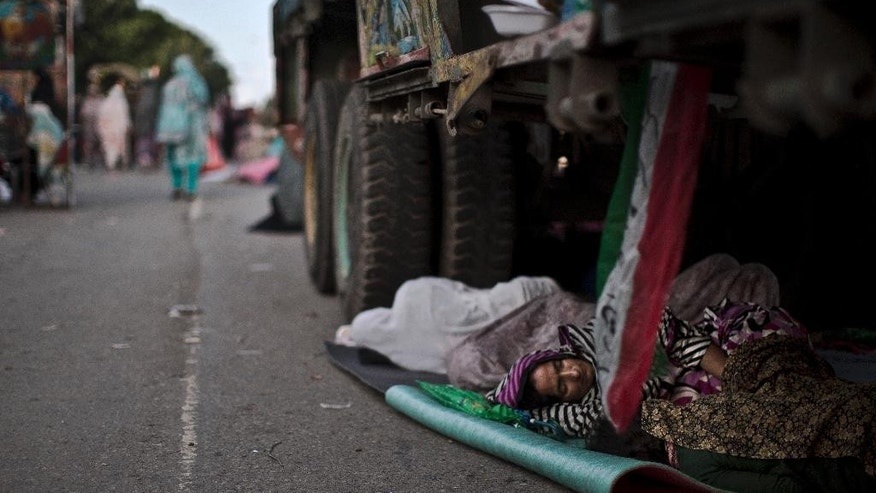 A supporter of anti-government cleric Tahir-ul-Qadri, sleeps on the ground under a truck, during a protest, in Islamabad, Pakistan, Sunday, Aug. 17, 2014. Qadri led massive rallies Saturday in Pakistan's capital, demanding Prime Minister Nawaz Sharif step down over alleged fraud in last year's election in front of thousands of protesters. (AP Photo/Muhammed Muheisen)