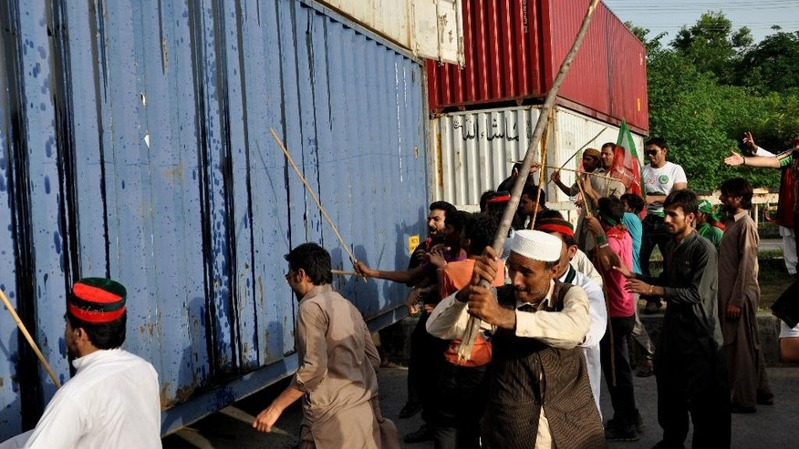 Supporters of Pakistan Tehreek-i-Insaf headed by cricketer-turned-politician Imran Khan beat shipping containers placed to stop protesters from entering into the high security zone in Islamabad, Pakistan, Sunday, Aug. 17, 2014. Khan has called upon protesters at an anti-government rally to practice civil disobedience. Khan led massive rallies in Pakistan's capital, demanding Prime Minister Nawaz Sharif step down over alleged fraud in last year's election. (AP Photo/B.K. Bangash)