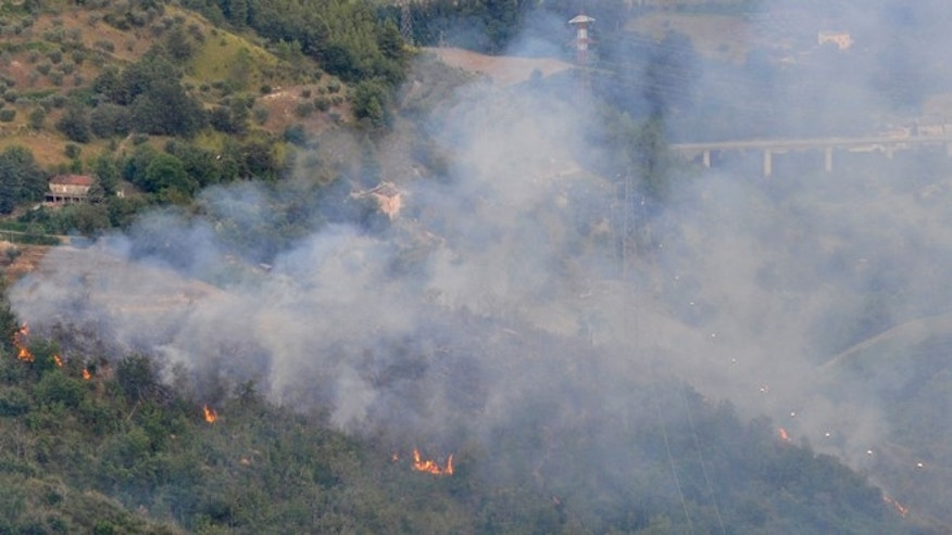 Aug. 19, 2014: Flames burn the bush after two Italian air force fighter jets carrying a total of four crew members collided during a training mission over Italy and crashed into a hilly, wooded area that erupted in flames, Tuesday, near Venarotta. It wasn't immediately known whether the two pilots and two navigators managed to eject from the Tornado jets.