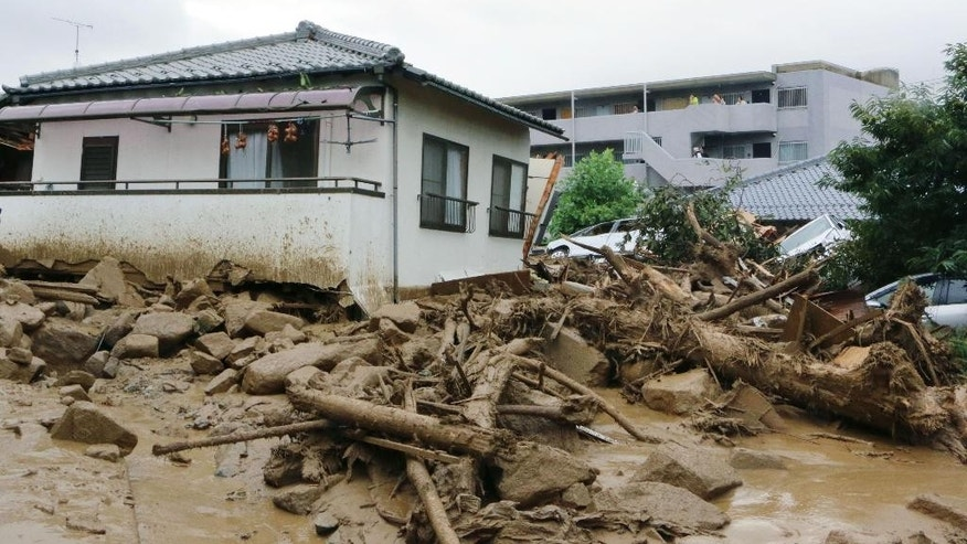 Half buried houses are seen following a massive landslides swept through residential area in Hiroshima, western Japan, Wednesday, Aug. 20, 2014. A several people died and at least a dozen are missing after rain sodden hills in the outskirts of Hiroshima gave way in at least five landslides, according to The Japanese broadcaster NHK. (AP Photo/Kyodo News, Shinpei Hamaguchi) JAPAN OUT, MANDATORY CREDIT