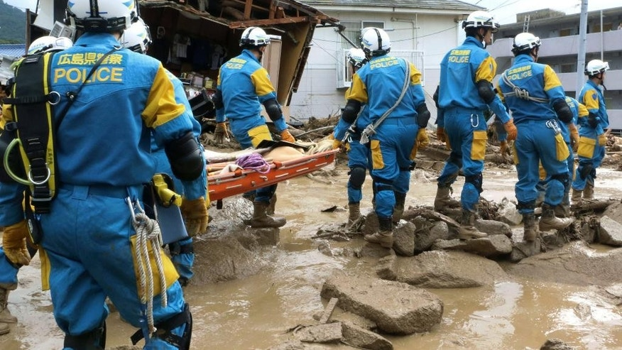 A troop of police rescue personnel head out for rescue operation after a massive landslides swept through residential area in Hiroshima, western Japan, Wednesday, Aug. 20, 2014. A several people died and at least a dozen are missing after rain sodden hills in the outskirts of Hiroshima gave way in at least five landslides, according to The Japanese broadcaster NHK. (AP Photo/Kyodo News, Shinpei Hamaguchi) JAPAN OUT, MANDATORY CREDIT
