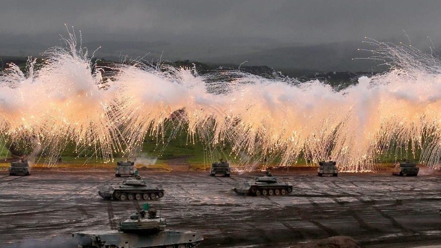 Japan Ground Self-Defense Force's Type-89 armored combat vehicles flare up a smoke screen during an annual live firing exercise at Higashi Fuji range in Gotemba, southwest of Tokyo, Tuesday, Aug. 19, 2014. (AP Photo/Shizuo Kambayashi)
