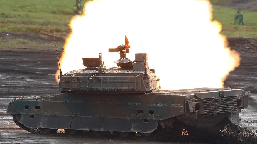 A Type-10 tank of the Japan Ground Self-Defense Force fires at targets during an annual live firing exercise at Higashi Fuji range in Gotemba, southwest of Tokyo, Tuesday, Aug. 19, 2014. (AP Photo/Shizuo Kambayashi)