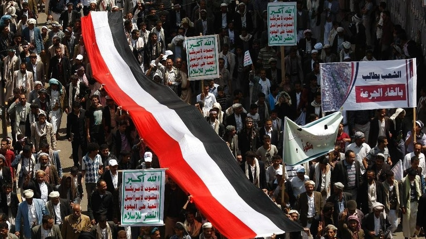 "Yemeni Shiite groups march during an anti-government demonstration in Sanaa, Yemen, Monday, Aug. 18, 2014. Arabic writing on a banner at right reads,""people demand to cancel the fuel prices hikes."" (AP Photo/Hani Mohammed)"