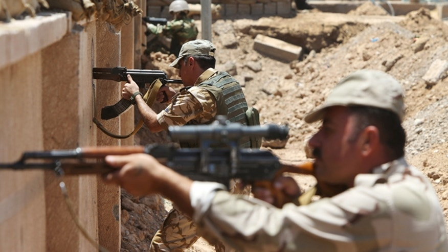 Kurdish Peshmerga fighters take their positions behind a wall on the front line with militants from Tuz Khormato, 62 miles south of the oil rich province of Kirkuk, northern Iraq.