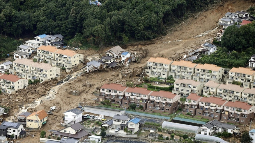 Aug. 20, 2014: In this aerial photo, a rescue helicopter hovers  over an area devastated by a massive landslide in Hiroshima, western Japan.