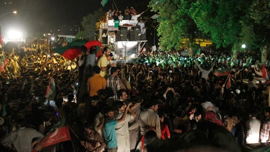 Thousands of supporters of Pakistan's cricketer-turned-politician Imran Khan march toward parliament in Islamabad, Pakistan, Wednesday, Aug. 20, 2014. Tens of thousands of protesters armed with wire cutters and backed by cranes broke through barriers protecting Pakistan's parliament and other government buildings Tuesday night, demanding the country's Prime Minister Nawaz Sharif resign. (AP Photo/Anjum Naveed)