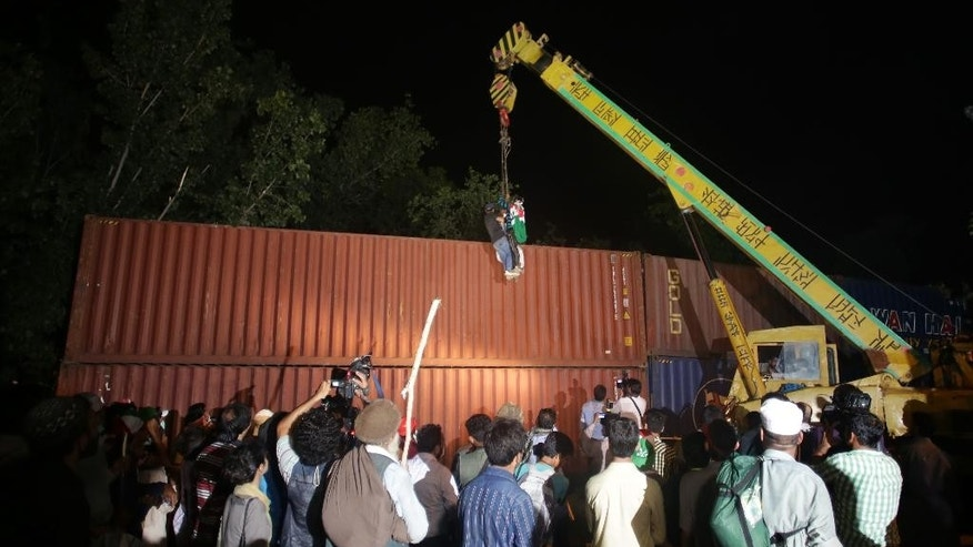 Supporters of Pakistani cleric Tahir-ul-Qadri prepare to remove shipping containers place by authorities to block their access as they try to reach the Parliament in Islamabad, Pakistan, Tuesday, Aug. 19, 2014. Tens of thousands of anti-government protesters armed with wire cutters and backed by cranes marched on Pakistan's parliament Tuesday, removing barriers blocking them from soldiers guarding the seat of the country's government. (AP Photo/B.K. Bangash)