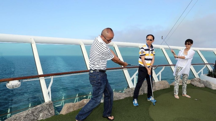 In this Wednesday, June 4, 2014 photo, Chinese tourists play mini golf on the Royal Caribbean cruise ship Mariner of the Seas during her voyage from Shanghai, China, to Jeju, South Korea. Cruise operators have traditionally sent older vessels to developing countries while saving their most advanced ships for U.S. and European customers. But surging growth in China means it's a market operators can no longer ignore. The race for China underscores the growing strength of the leisure and travel industries in the world's No. 2 economy as authorities try to spur domestic spending rather than trade and investment as an engine of growth. (AP Photo) CHINA OUT