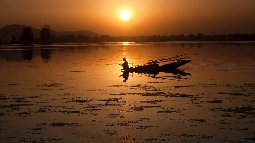 A Kashmiri fisherman rows his Shikara, or traditional boat, during sunset at the Dal Lake in Srinagar, India, Tuesday, Aug. 19, 2014. Both India and Pakistan control parts of Kashmir and claim it in its entirety. In a blow to efforts to improve often-hostile ties, India on Monday called off talks with Pakistan over a meeting between its ambassador and Kashmiri separatists. (AP Photo/Dar Yasin)