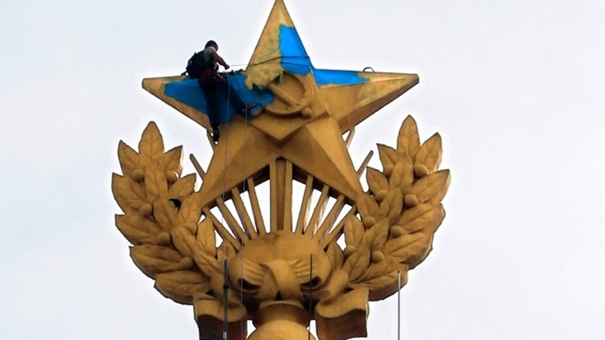 Aug. 20, 2014: A man paints yellow over the blue at one of Moscow's Stalin-era skyscrapers with a star on top, which was painted in colors of the Ukrainian national flag in Moscow, Russia.