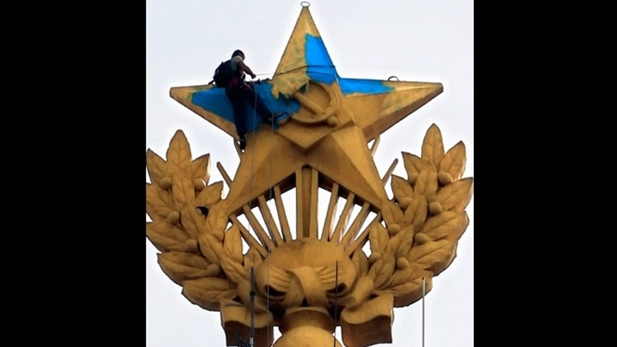 Aug. 20, 2014: A protester paints yellow over the blue at one of Moscow's Stalin-era skyscraper with a star on top, which was painted in colors of Ukrainian national flag in Moscow, Russia.