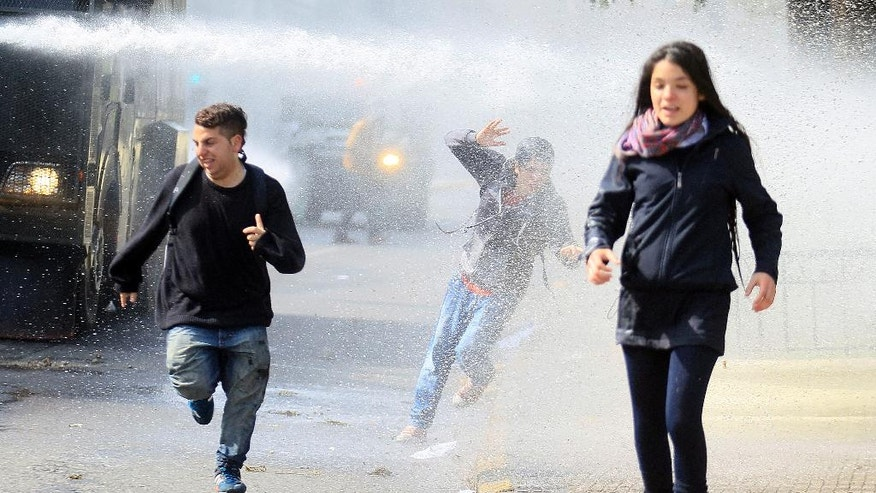 Young protesters run away from a water cannon, during a student protest in Santiago, Chile, Thursday, Aug. 21, 2014. Tens of thousands of students protested in the third massive march of the year in Chile. The students are unhappy with the pace of education reform that President Michelle Bachelet has been moving forward. (AP Photo / Luis Hidalgo)