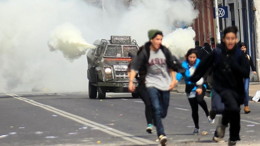 Protester run away from on oncoming tear gas truck, during a student protest march in Santiago, Chile, Thursday, Aug. 21, 2014. Tens of thousands of students protested in the third massive march of the year in Chile. The students are unhappy with the pace of education reform that President Michelle Bachelet has been moving forward. (AP Photo/Luis Hidalgo)