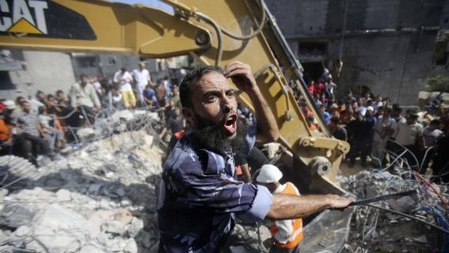 August 21, 2014: A Palestinian policeman reacts as rescue workers search for victims under the rubble of a house, which witnesses said was destroyed in an Israeli air strike, in Rafah in the southern Gaza Strip. (Reuters/IBRAHEEM ABU MUSTAFA)